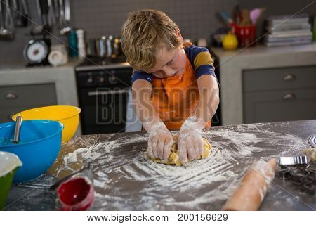 Boy kneading dough at counter in kitchen