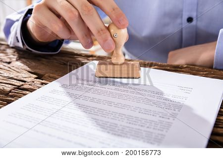 Person Holding Stamp On Document Over Wooden Desk