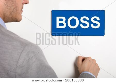 Close-up Of A Young Businessman Knocking White Door With Boss Text