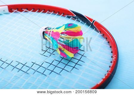Close-up of badmington rackets with balls on a blue background.