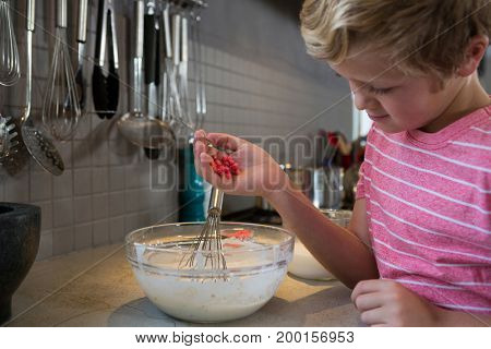 Boy holding sweet food over batter bowl at kitchen counter