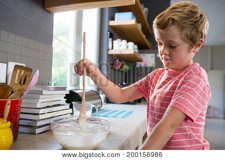 Boy mixing batter at kitchen counter