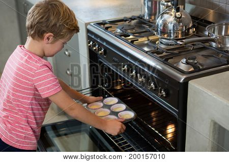Boy holding muffin tin by oven in kitchen at home