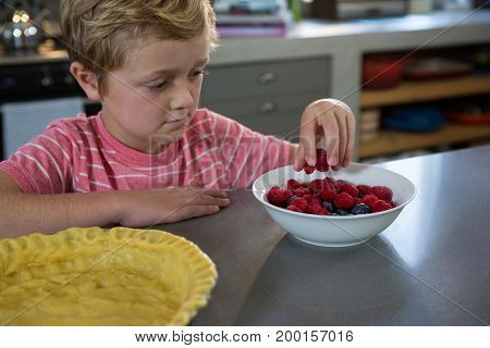 Boy having raspberries at kitchen counter