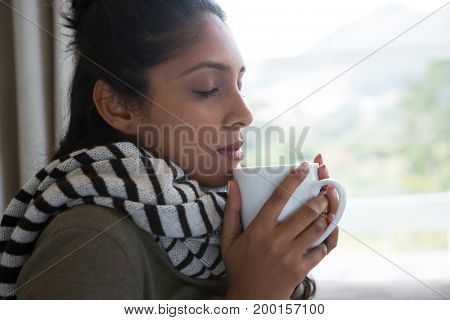 Woman with eyes closed holding coffee cup by window at home