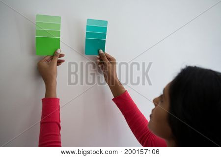 Young woman holding color swatches by wall at home
