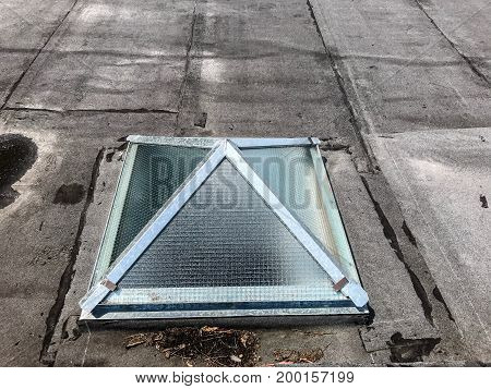 Small skylight window on the roof of an old building.