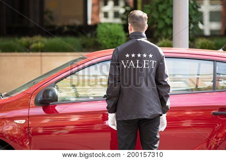 Rear View Of A Valet Standing In Front Of Red Car