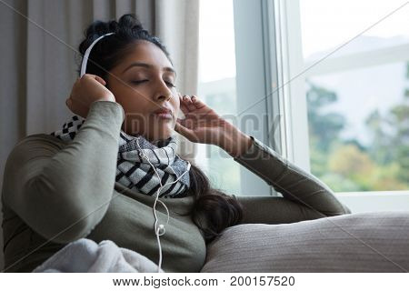 Relaxed woman listening to music by window at home