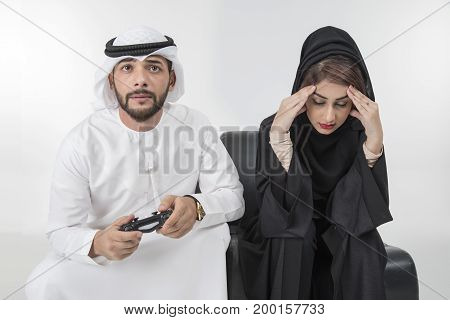 Arab Man is playing playstation computer game woman girlfriend is angry for him