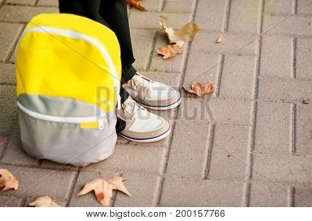 The school boy is ready to go to school. The legs are on the sidewalk, the backpack is near. Concept of education