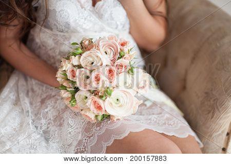 seating bride holding wedding flower bridal bouqet