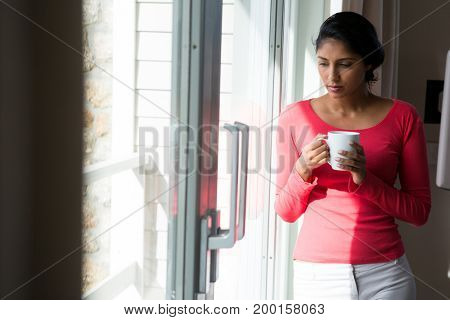 Thoughtful young woman with coffee cup by window at home