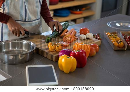 Mid section of woman cutting zucchini at kitchen counter