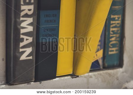 Language book on a book shelf. One book pulled out.