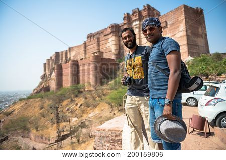 JODHPUR RAJASTHAN INDIA - MARCH 05 2016: Horizontal picture of two indian tourists posing in front of Mehrangarh Fort in Jodhpur the blue city of Rajasthan in India.