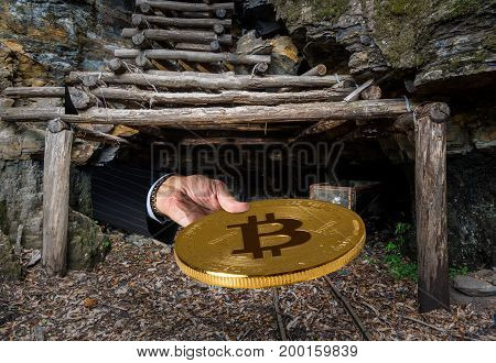 Miner engaged in mining for new bitcoins holds out a coin out of the entrance to an old coal mine