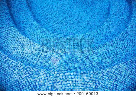 Round steps into the pool from the mosaic in blue shades.