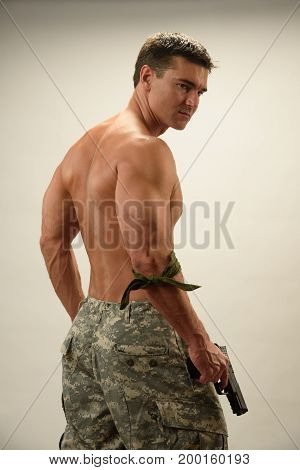 The handsome army man stands in a back pose.