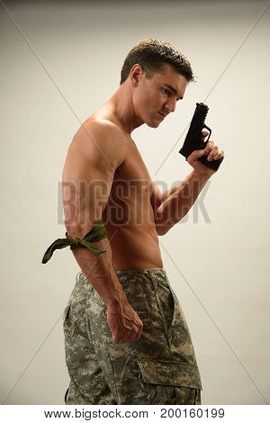 The handsome warrior is posing with a pistol.
