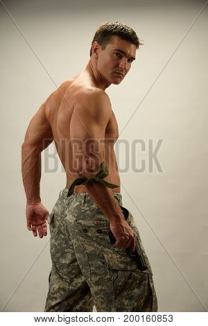 The handsome army man stands flexing his back.