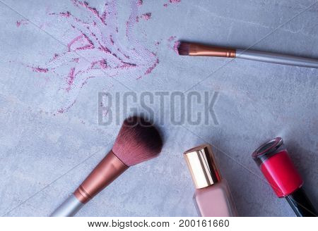 Beauty products everyday makeup vibrant background. Cosmetic essentials on a gray marble background top view