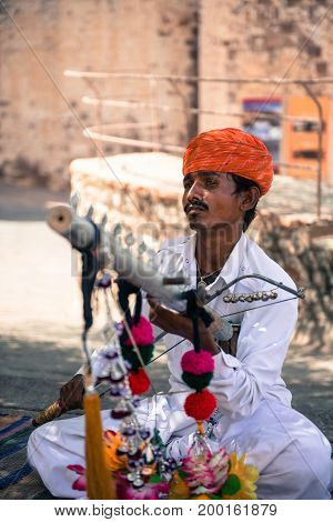 JODHPUR RAJASTHAN INDIA - MARCH 05 2016: Vertical picture of local indian with mustache playing music inside Mehrangarh Fort in Jodhpur the blue city of Rajasthan in India.