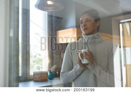 Thoughtful woman with coffee cup seen through glass in kitchen at home