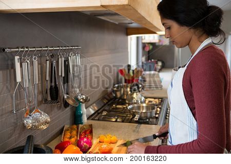 Side view of woman cutting vegetables in kitchen at home