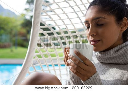 Woman holding coffee cup while relaxing in swing chair at poolside