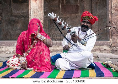 JODHPUR RAJASTHAN INDIA - MARCH 05 2016: Close picture of indian couple playing local music inside Mehrangarh Fort in Jodhpur the blue city of Rajasthan in India.
