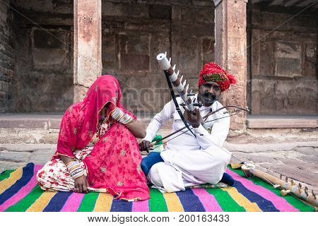 JODHPUR RAJASTHAN INDIA - MARCH 05 2016: Wide angle picture of indian couple playing local music inside Mehrangarh Fort in Jodhpur the blue city of Rajasthan in India.