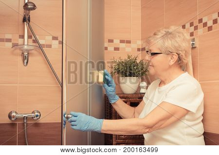 Senior Woman Using Sponge And Cleaning Shower, Household Duties Concept