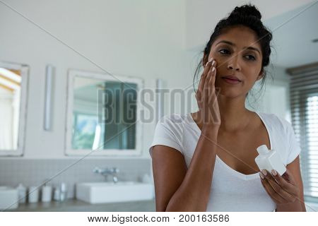 Young woman applying lotion in bathroom at home