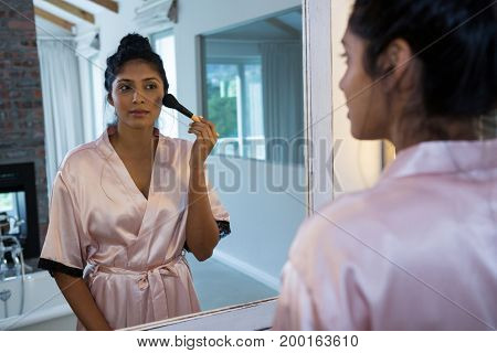 Young woman applying blush makeup with reflection on mirror at home