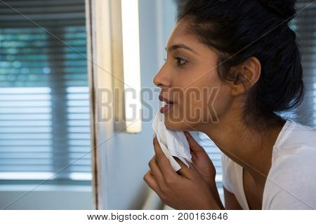 Young woman wiping face in bathroom at home