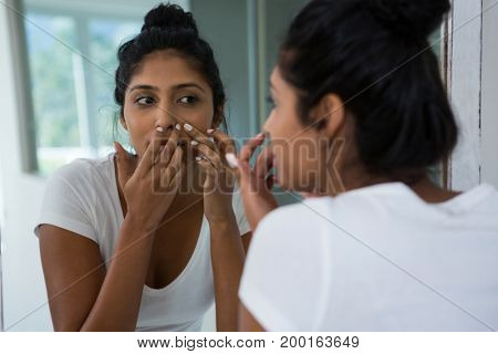 Woman squeezing pimple reflecting on mirror in bathroom at home