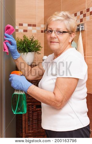Elderly Senior Woman Cleaning Shower Using Microfiber Cloth And Detergent, Household Duties Concept