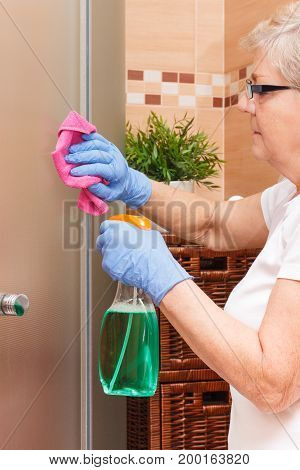 Hand Of Senior Woman Cleaning Glass Shower In Bathroom, Household Duties Concept