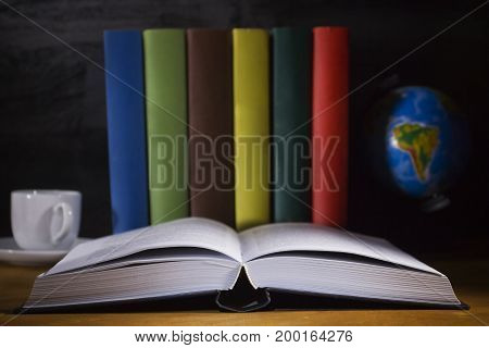Open book and colorful books on a wooden table