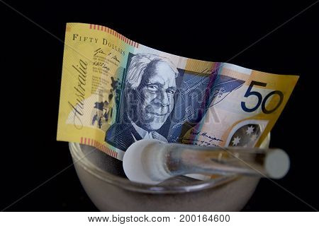 Australian fifty dollar note in a glass mortar with a pestle.