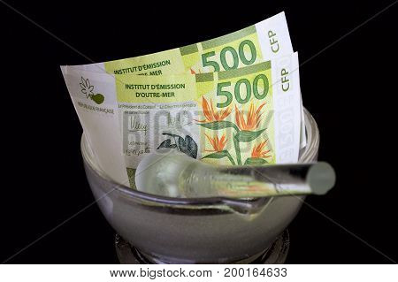 Five hundred Polynesian francs in a mortar with a pestle.