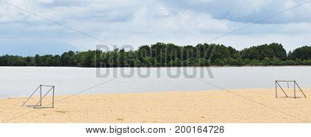two goal on beach beside sea under blue sky