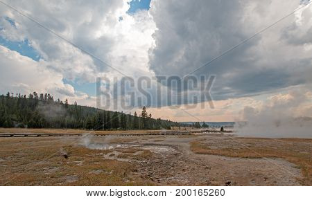 Steam rising off Black Warrior hot springs geyser and Hot Lake under cumulus clouds in Yellowstone National Parks Lower Geyser Basin in Wyoming United States