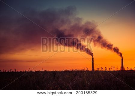 Industrial smoke from chimney at sunset steppe near Almaty Kazakhstan.