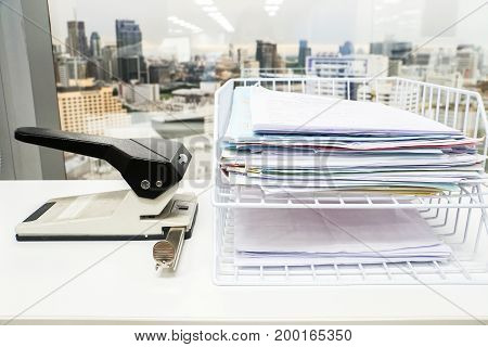 business documents stack in box with big paper punch in office