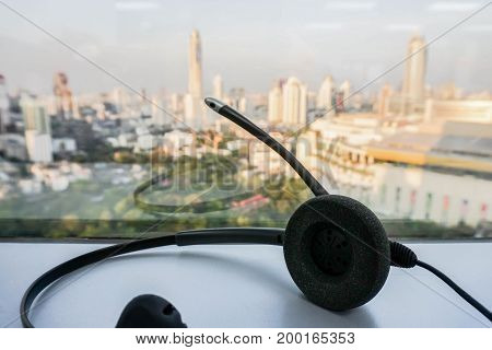 close up black headset on table with city view backdrop
