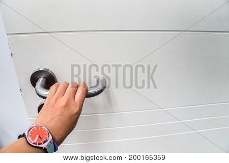 isolated woman hold doorknob for open the door with left hand