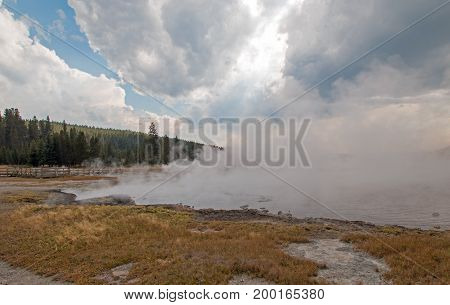 Steam rising off Black Warrior hot springs geyser and Hot Lake in Yellowstone National Parks Lower Geyser Basin in Wyoming United States