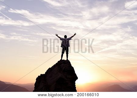 Man with arms raised in the sky winner success concept